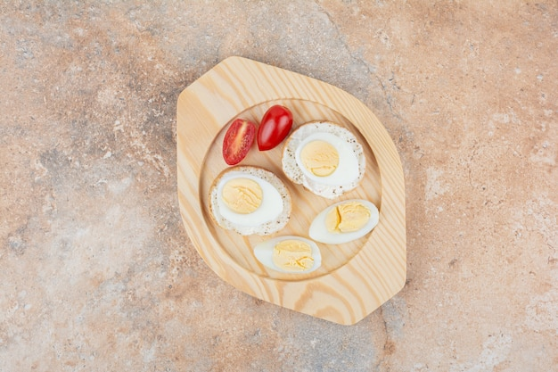 Bread slices with boiled eggs and tomato on wooden plate