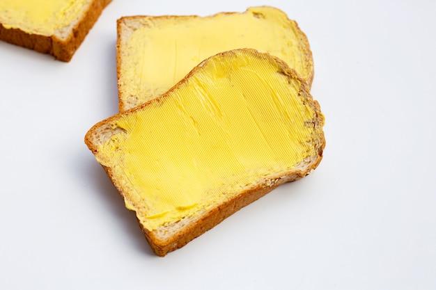 白い背景にバターとパンのスライス。
