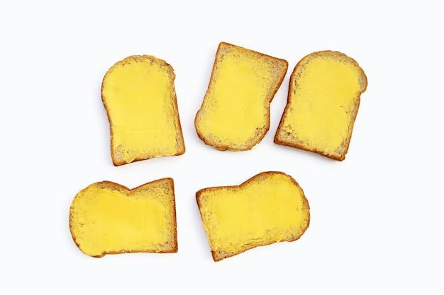 白い背景の上のバターとパンのスライス。