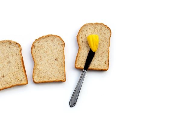 白い表面にバターを塗ったパンのスライス