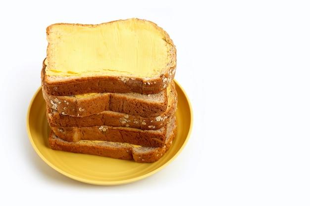 白いテーブルにバターとパンのスライス。