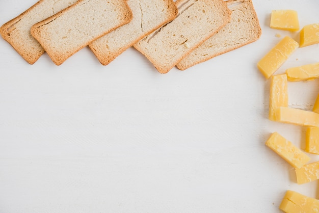 Bread slices with cheddar cheese slice on white background