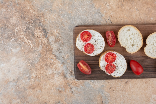 Bread slices with cream and tomato on wooden board