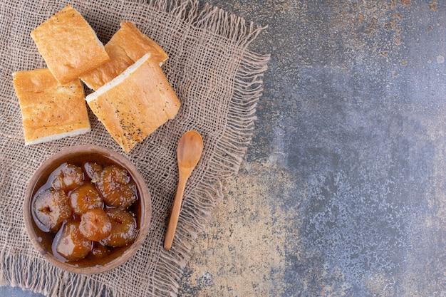 Fette di pane con una tazza di confettura di fichi