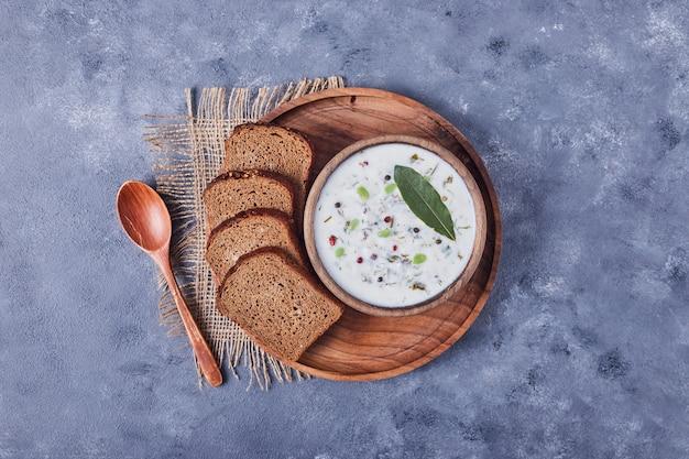 Fette di pane con una tazza di zuppa di yogurt e foglia di origano.