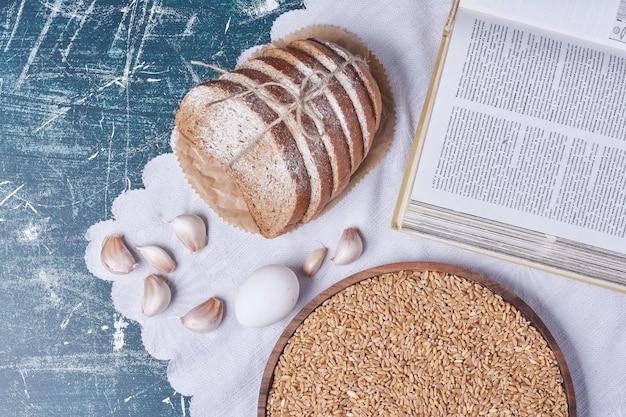 青いテーブルの上に卵とニンニクとパンのスライス。