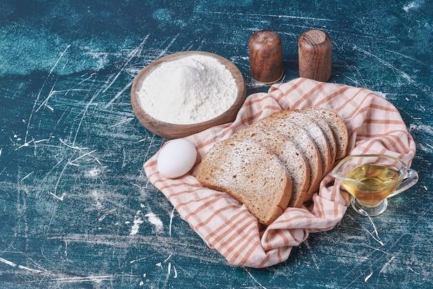青いテーブルに卵と油でスライスしたパン。