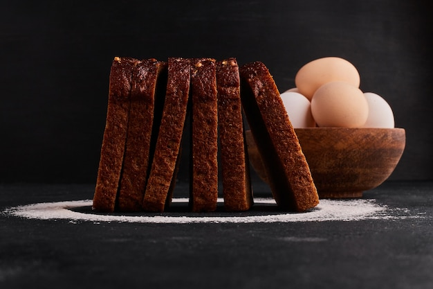 밀가루와 계란 주변, 측면보기와 빵 조각.