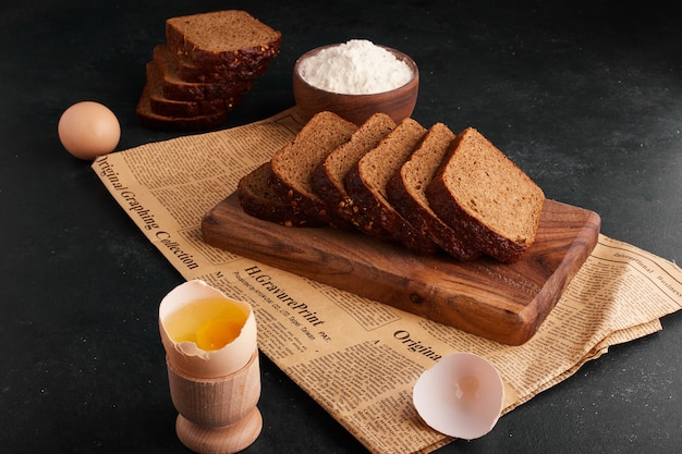 Bread slices with ingredients on the wooden board.