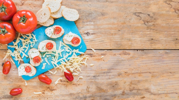Bread slices with tomatoes and grated cheese on wooden table