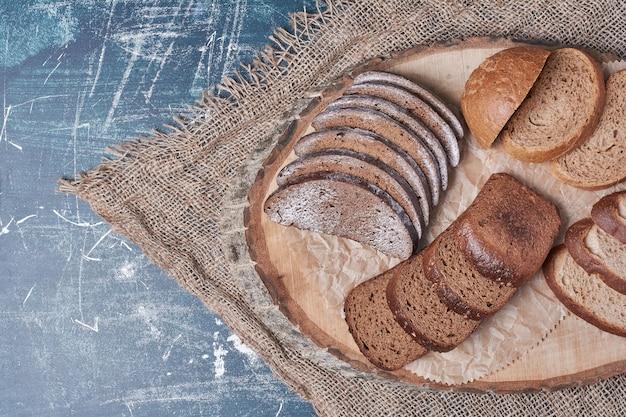 Fette di pane sulla tavola di legno sulla tavola blu.