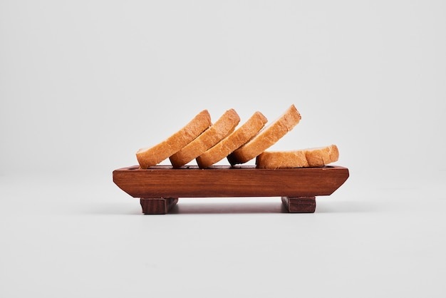 Bread slices on wooden board.