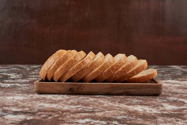 Bread slices on wooden platter.
