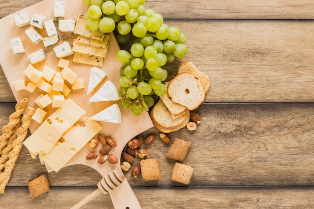 Bread sticks, cheese blocks, grapes, bread and cookies on wooden desk