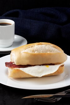 Bread stuffed with egg and bacon served with a black coffee.