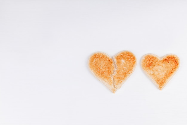 Bread toast broken heart with whole heart together on white background