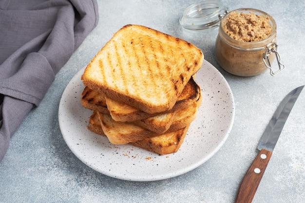 グレーのコンクリート テーブルの上の皿に、サンドイッチ用のカリカリのパン トースト。チキンパテの瓶。