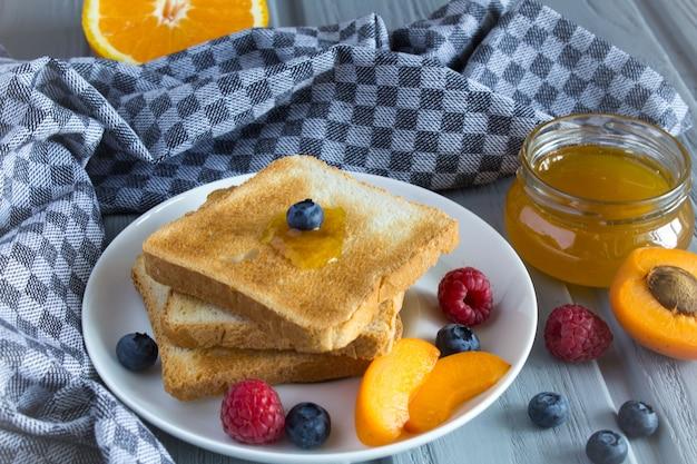 Хлебный тост с абрикосовым джемом и фруктами на сером деревянном фоне
