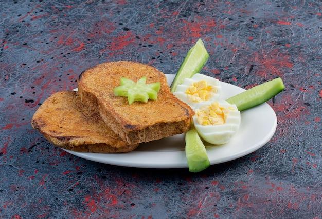 Pane tostato con uova sode e cetrioli.