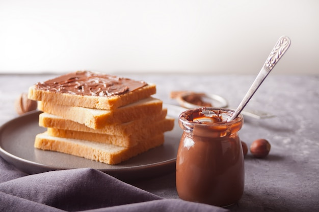 Bread toast with chocolate cream butter, jar of chocolate cream