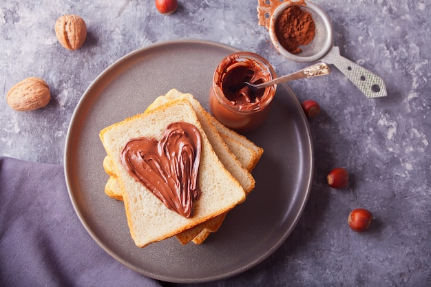 Bread toast with heart shaped chocolate cream butter, jar of chocolate cream