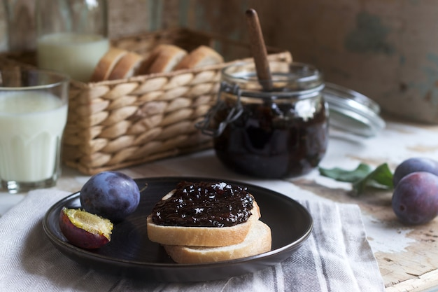 Bread toast with plum jam, served with milk and plums. rustic style.