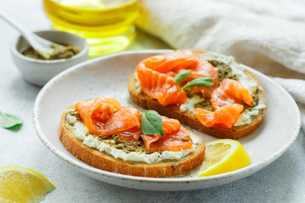 Bread toast with salted salmon, pesto sauce, lemon and cream cheese (ricotta)