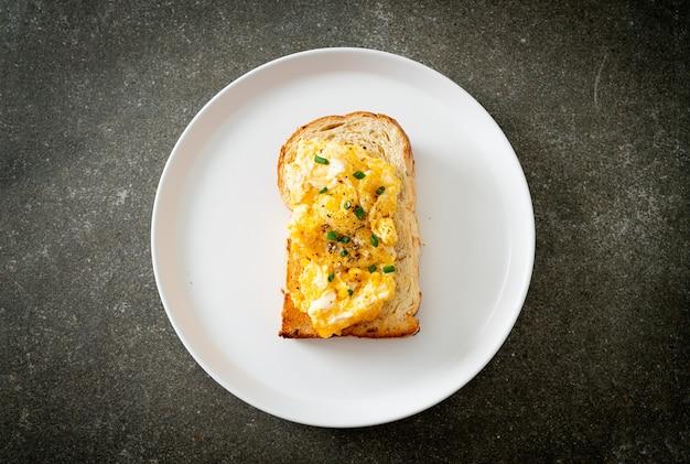 Хлебный тост с яичницей на белой тарелке