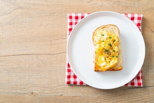 하얀 접시에 스크램블 에그를 곁들인 빵 토스트