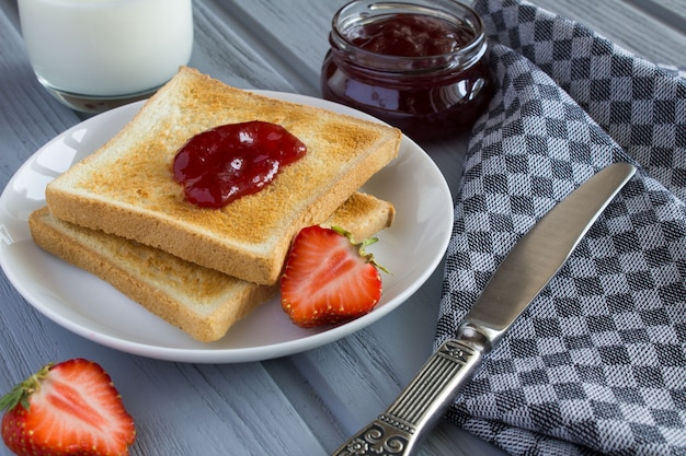 Bread toast with strawberry jam and milk