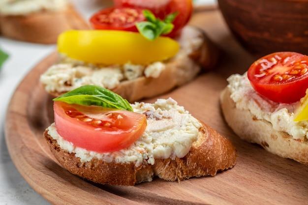 木の板にトマト、クリームチーズ、バジルを添えたパントースト。健康食品のトレンド
