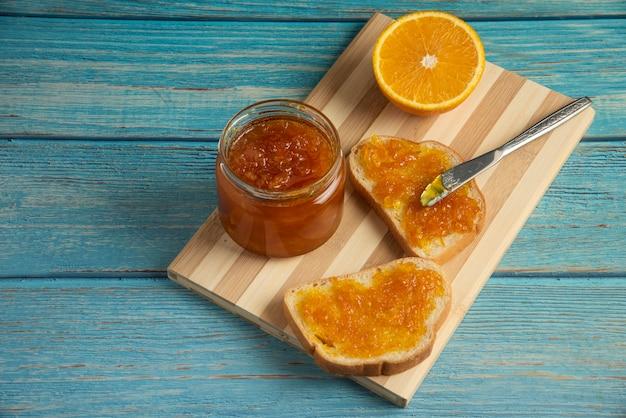 木の板にオレンジ色のコンフィチュールを添えたパンのトースト。