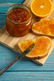 Bread toastes with orange confiture on wooden board.