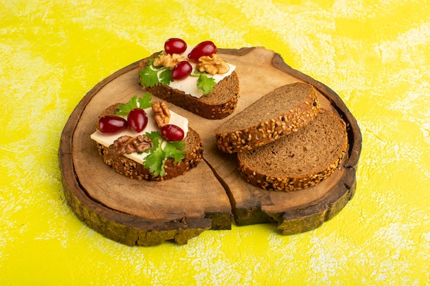 Bread toasts with cheese walnuts and dogwood on yellow