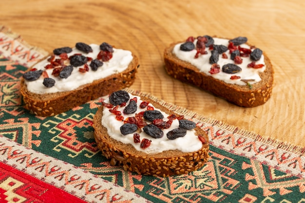 Bread toasts with dried fruits and cream on wood