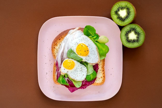 Bread toasts with fried eggs and green salad