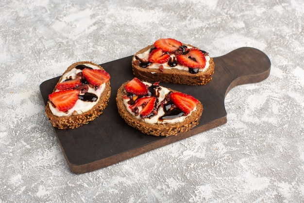 Bread toasts with sliced strawberries and cream on grey