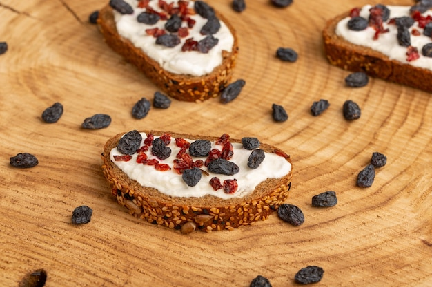 Bread toasts with sour cream and dried fruits on wood