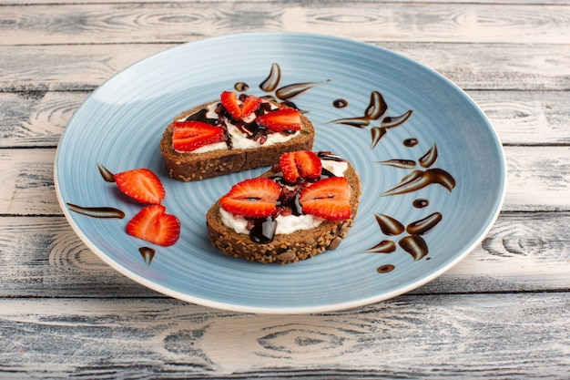Bread toasts with sour cream and sliced strawberries on wood