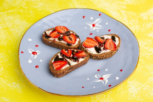 Bread toasts with sour cream and strawberries inside blue plate on yellow