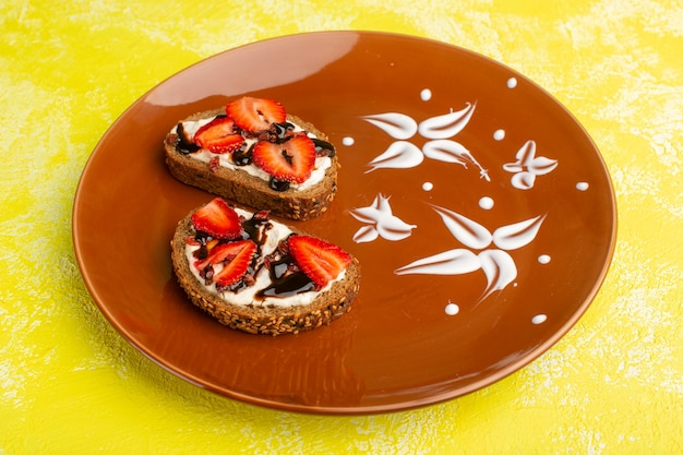 Bread toasts with sour cream and strawberries inside brown plate on yellow