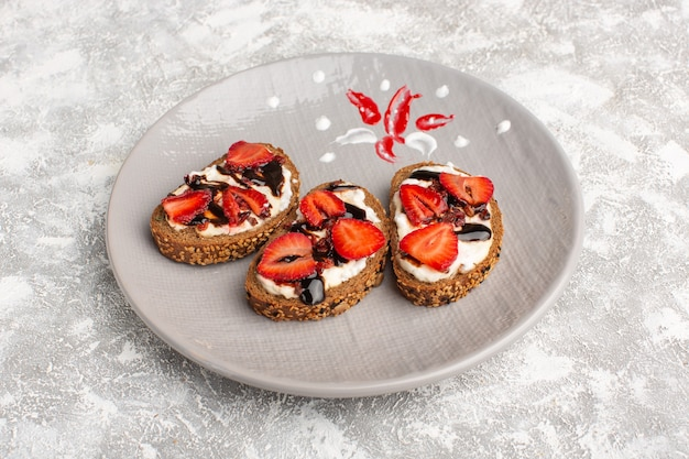 Bread toasts with strawberries and sour cream inside plate on grey