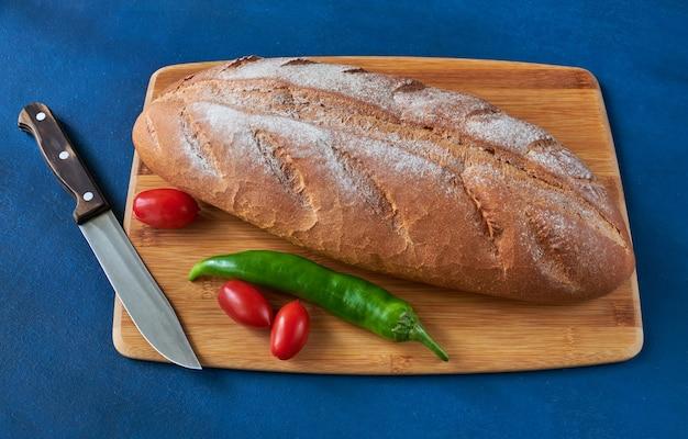 빵, 토마토, 고추 후추, 칼이 도마 위에 놓여 있고, 얕은 피사계 심도, 정물