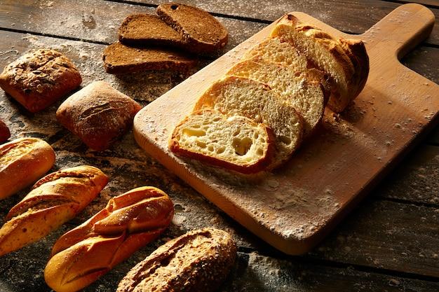 Bread varied loafs sliced on wood board in rustic