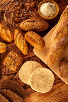 黄金の熟成木のテーブルにパンの様々なミックス
