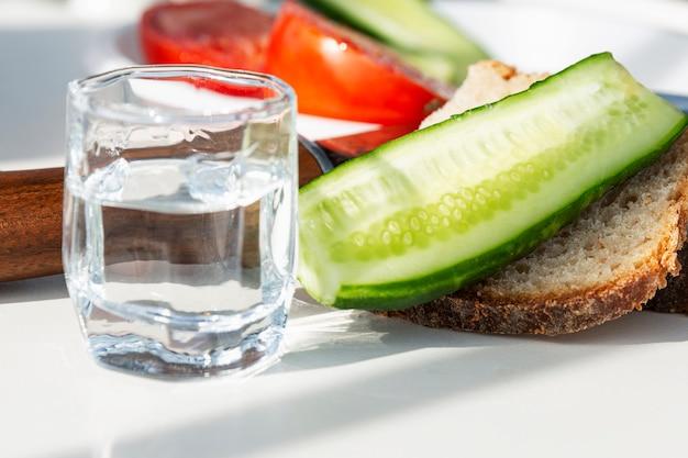 Хлеб, овощи и стакан водки на столе. закуска из свежих огурцов и помидоров. крупный план.