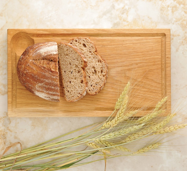 Bread and wheat ears on wooden board