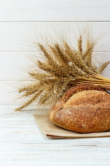 Bread and wheat on white wooden background