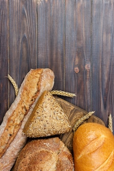 Bread and wheat on white wooden.