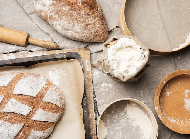 Bread and  white wheat flour in a bag, wooden rock and plate, top view